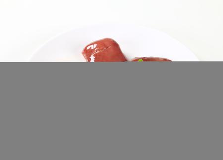higado de pollo: H�gado de pollo sin procesar en la placa blanca Foto de archivo