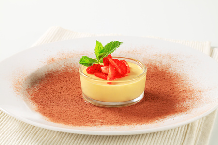 Small dish of custard topped with strawberry photo