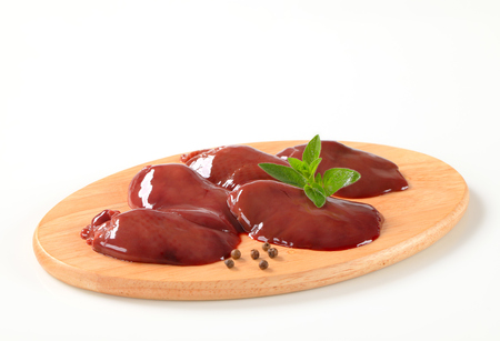 higado de pollo: H�gado de pollo crudo en la tabla de cortar