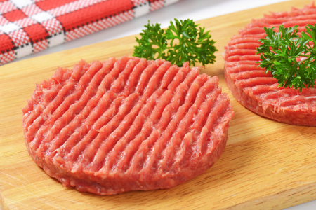 mincing: detail of two raw hamburger patties with parsley on wooden cutting board