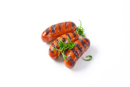 three grilled sausages on white background photo