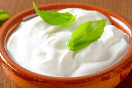 white yogurt or sour cream in a ceramic bowl