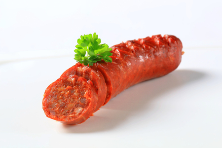 high calorie: Spicy dry sausage on white plate Stock Photo
