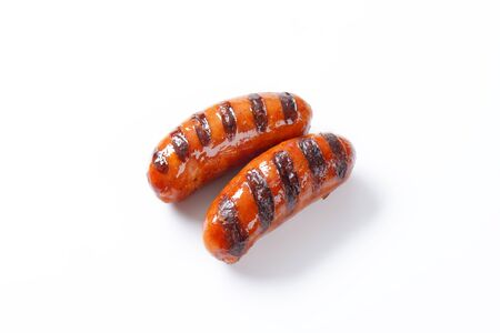 two grilled sausages on white background photo