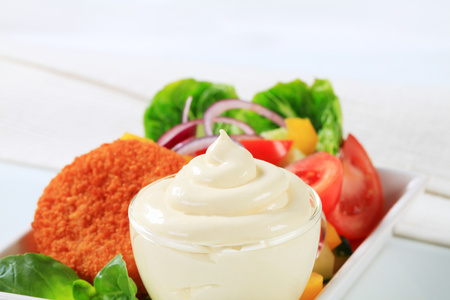 gronostaj: Creamy mayonnaise in a cup with fried cheese and vegetable salad in the background