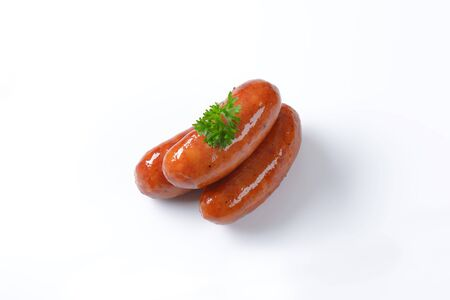 pan fried: three pan fried sausages on white background Stock Photo