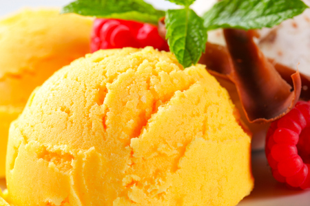 chocolate curls: Scoops of yellow ice cream with raspberries and chocolate curls