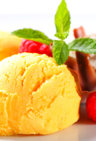 curls: Scoops of yellow ice cream with raspberries and chocolate curls
