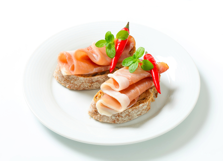 faced: Prosciutto open faced sandwiches garnished with red chili peppers