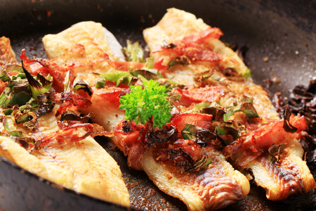 Pan fried fish fillets with bacon and spring onion photo