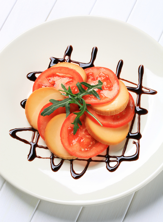 balsamic vinegar: Sliced tomato and smoked cheese garnished with balsamic vinegar
