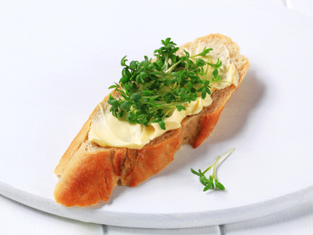 Slice of baguette with butter and cress