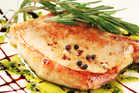 drizzle: Pan fried pork chop decorated with pesto sauce and balsamic drizzle