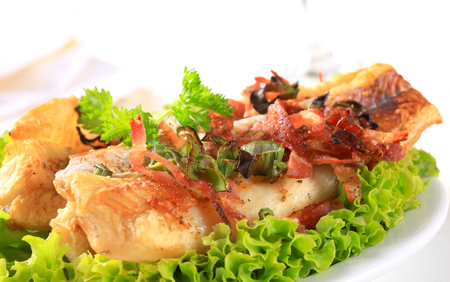 bacon bits: Pan fried fish fillets sprinkled with crispy bacon bits Stock Photo