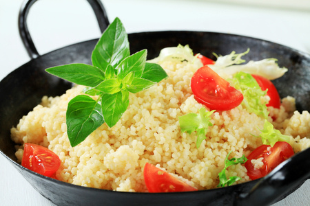 salad greens: Couscous with salad greens and tomato in a pan