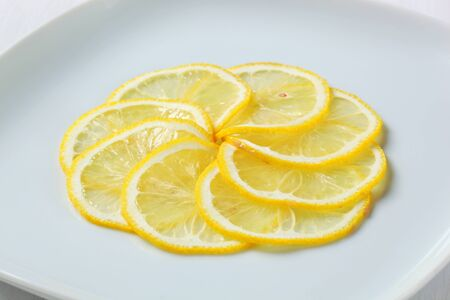 thinly: Thinly sliced lemon on plate Stock Photo