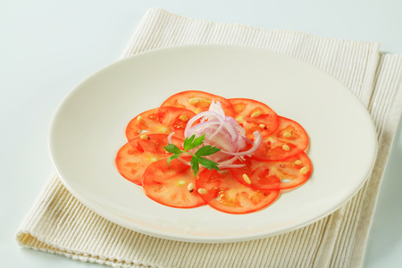 thinly: Thinly sliced tomato with onion and pine nuts