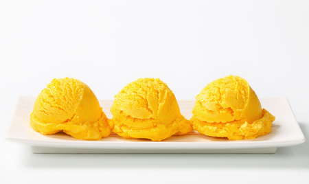 serving dish: Three scoops of ice cream on a long serving dish