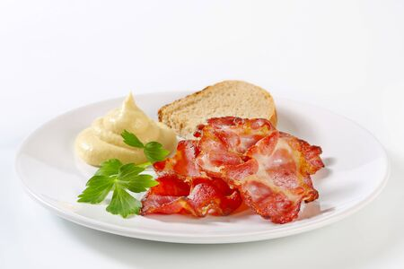 dollop: Crispy bacon slices with bread and mustard sauce Stock Photo