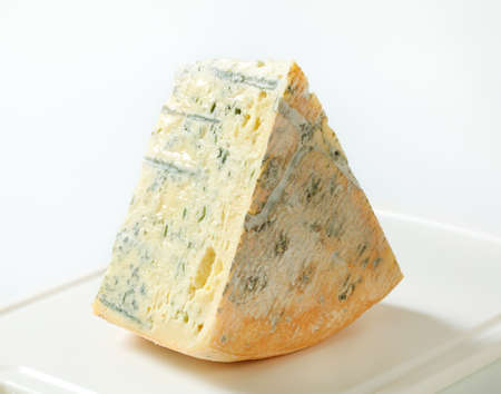 wedge: Large wedge of blue cheese on a cutting board