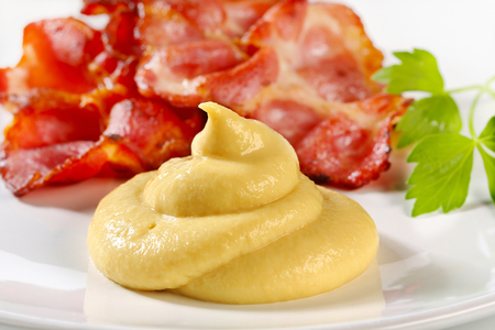dollop: Pan fried bacon slices and mustard sauce Stock Photo