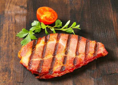 dark brown: Grilled pork steak on dark brown wood