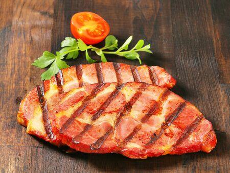 dark brown: Grilled pork steaks on dark brown wood Stock Photo