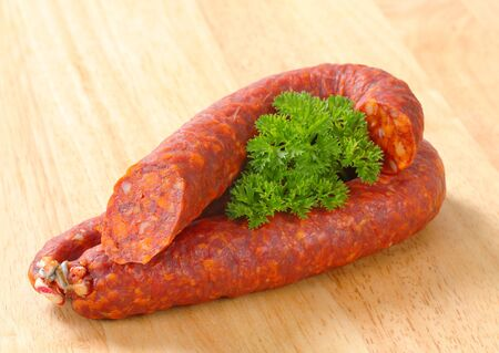 dry sausage: Spicy dry sausages on wooden background