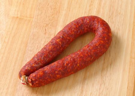 dry sausage: Spicy dry sausage on wooden background Stock Photo