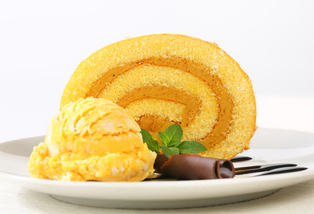 cakes and pastries: Slice of Swiss roll with yellow ice cream and chocolate sauce