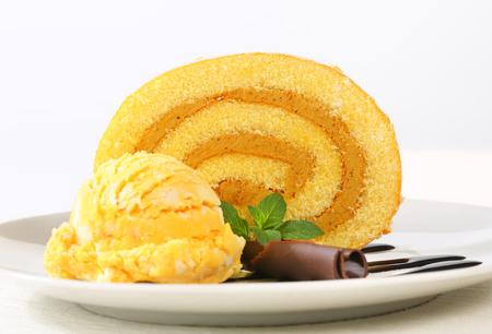 swiss roll: Slice of Swiss roll with yellow ice cream and chocolate sauce
