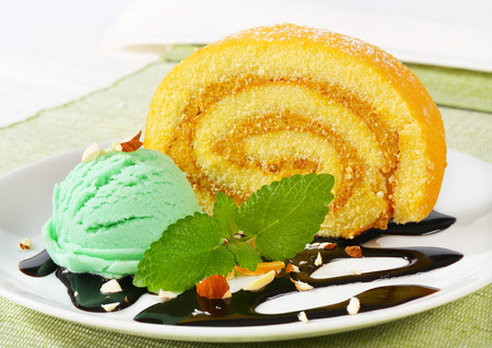 swiss roll: Slice of Swiss roll cake with green sherbet and chocolate sauce