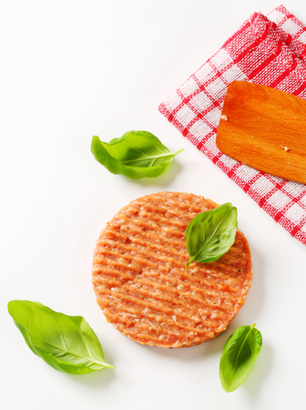 patty: Raw burger patty with fresh basil leaves
