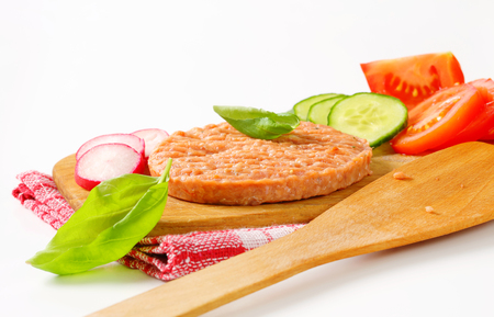 patty: Raw burger patty and sliced vegetables on cutting board Stock Photo