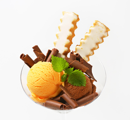 chocolate curls: Scoops of ice cream decorated with chocolate curls and vanilla cookies Stock Photo