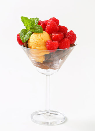 chocolate curls: Scoops of ice cream topped with chocolate curls and raspberries Stock Photo