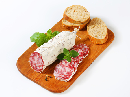 french roll: French Saucisson Sec and sliced crispy roll on cutting board