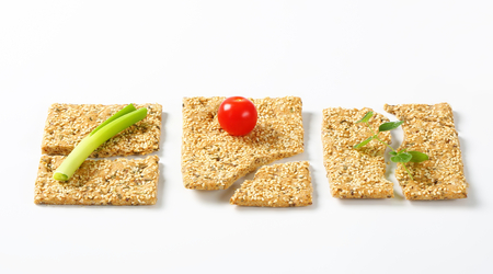 whole wheat: Whole wheat crackers with sesame seeds and chopped herbs Stock Photo