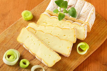 artisanal: French soft cheese with chopped leek on cutting board