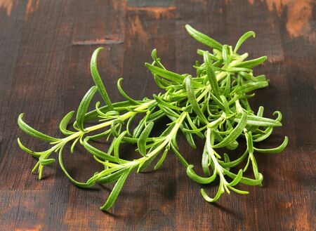 sprigs: Fresh rosemary sprigs on wooden background