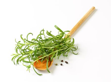 sprigs: Fresh rosemary sprigs, peppercorns and wooden spoon Stock Photo