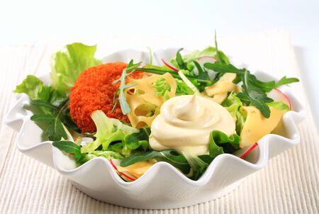 swiss cheese: Green salad with fried breaded cheese and sliced Swiss cheese and mayonnaise Stock Photo