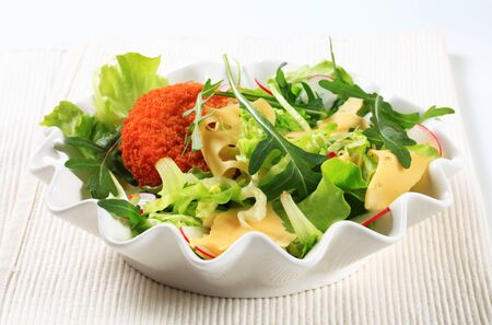 swiss cheese: Green salad with fried breaded cheese and sliced Swiss cheese Stock Photo