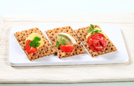 whole grain: Whole grain crisp bread slices with various toppings