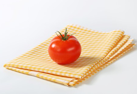 dishcloth: Fresh red tomato on checked yellow tea towel Stock Photo