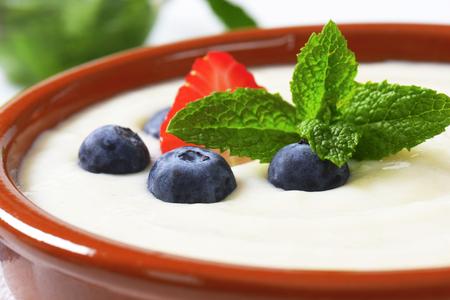 semolina: Smooth semolina porridge served in terracotta dish with fresh fruit Stock Photo
