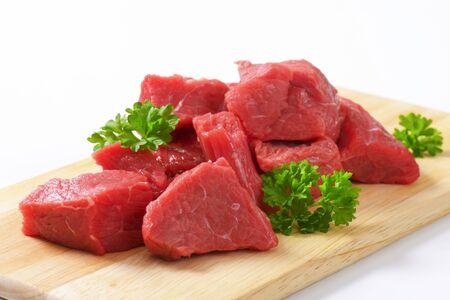 Raw diced beef on cutting board