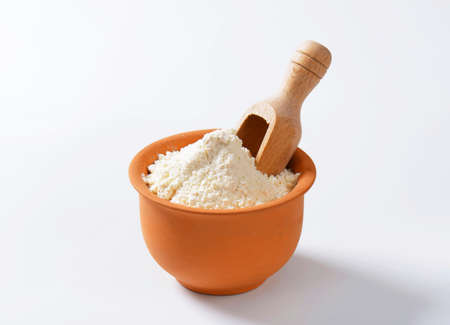 wooden scoop: Finely ground flour and wooden scoop in terracotta bowl