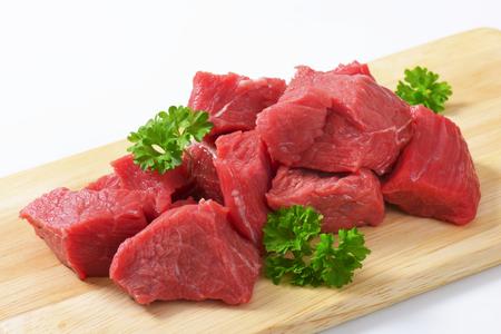 carne de res: Carne de vaca cortada en cuadritos sin procesar en la tabla de cortar