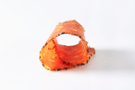 thinly: Black pepper-coated salami speckled with pieces of Comte cheese - thinly sliced Stock Photo